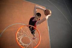 Basketballstraßenspieler, der einen Slam Dunk macht Stockfotografie
