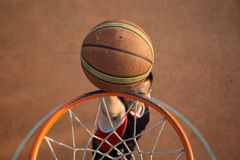 Basketballstraßenspieler, der einen Slam Dunk macht Stockbild