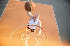 Basketballstraßenspieler, der einen Slam Dunk macht Stockfoto