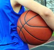Basketbalspeler die blauwe eenvormig met de bal dragen stock foto