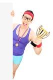 Basketbalspeler die een trofee achter een paneel houden Royalty-vrije Stock Afbeeldingen