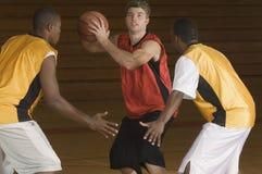 Basketbalspeler met Bal die door Tegenstanders worden geblokkeerd Stock Fotografie