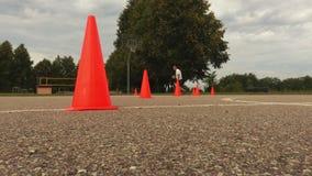 Basketbalspeler opleidingsdribble element tussen de kegels stock videobeelden