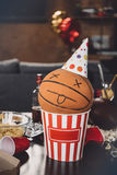 Basketboll med den roliga framsidan i popcornask och smutsig tabell efter parti Arkivfoto
