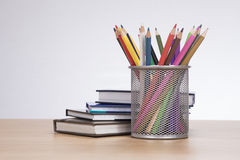Basketful of colored pencil crayons with books. Basketful of colored pencil crayons in a wire mesh container with a pile of stacked books alongside on a wooden Stock Photo