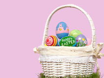 Basketful of colorful Easter eggs against purple Stock Photography