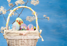 Basketful of colorful Easter eggs on blue backgrou Royalty Free Stock Photos