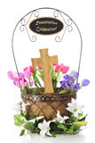 Basketful of Easter. A basket containing a wooden cross and surrounded by colorful tulips.  It's surrounded by Easter lillies and the handle contains a sign Royalty Free Stock Photo