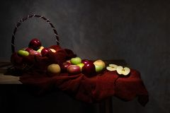 Basketful of various type of apples. With some on the wooden table and one of them is cut in to half stock image