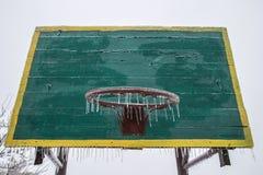 Basketmålbräda och cirkel i vinter Med hängande istappar för ett basketbeslag is Glasera inga sportar Inga lekar Arkivfoto