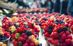 Baskets of berries at the farmers market. Yellow red raspberries and blackberries at a farmer s market Royalty Free Stock Photography