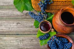 Baskets and bowl with grapes beside Jar and cup with wine stand on on rustic wood. Wine making background. Stock Photo