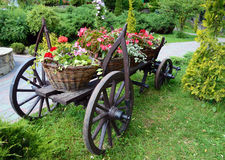 Baskets of flowers on ancient peasant cart on a sunny day Royalty Free Stock Photos