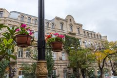 Baskets with flowers on a column, streetscape Stock Photos