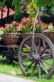 Baskets of flowers and wheel of ancient peasant cart on a sunny Stock Photos
