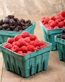 Baskets of fresh red raspberries and black raspberries Royalty Free Stock Images