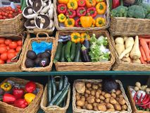 Fresh vegetable market stall. Baskets full of fresh organic fruit and vegetables including tomatoes, carrots and mushrooms and have been organically grown by royalty free stock photo