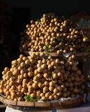 Baskets full of tropical longan fruit. Under morning light at the street market, Vietnam Royalty Free Stock Images
