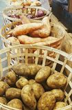 Baskets of organic vegetables. Potato, sweet potato and onions in baskets for sale at market Stock Photo