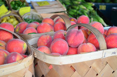 Baskets of Peaches Closeup. Closeup of baskets of fresh peaches and background with blurred vegetables Royalty Free Stock Photo