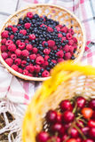Baskets of raspberries, blueberries and cherries on a tablecloth on a picnic. Wild berries on a picnic Royalty Free Stock Photography
