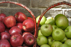 Baskets of Red and Green Apples. Red Apples in a basket next to Green Apples in a basket out side in the sun with a brick wall in the background Stock Photography