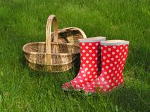 Baskets and wellingtons. Two baskets and white-dotted red gumboots on the green grass Royalty Free Stock Photography