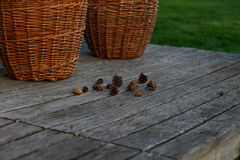 Baskets with wood and pine cones on wooden background Stock Photos