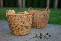 Baskets with wood and pine cones on wooden background Stock Photo