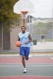 Basketspelare som kör och dreglar bollen Royaltyfri Bild