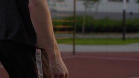 Basketspelare som studsar bollen på övning arkivfilmer