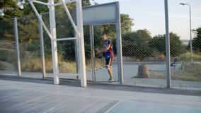 Basketspelaren kommer till lekplatsen för leken Basketspelaren spelar på gryningen av solen lager videofilmer