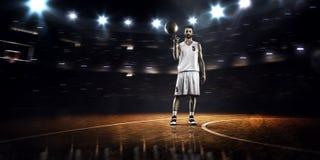 Basketspelaren rotera bollen runt om Arkivbild