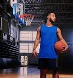 Basketspelaren rymmer en boll över beslaget i en modig korridor royaltyfri bild