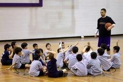 Baskettränare med studenter i idrottshallen Fotografering för Bildbyråer