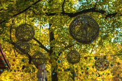 Basketwork wicker decorative balls. Hung amidst yellow leaves on the branches of trees Stock Photo