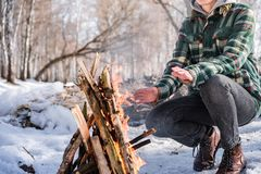 Basking near a campfire in a snowy birch forest royalty free stock photo
