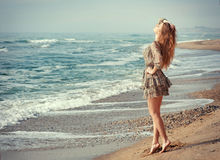 Basking in the sunshine. Beautiful svelte woman standing at the seaside and basking in the sunshine Royalty Free Stock Images