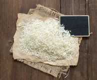 Basmati raw rice on wood with a small chalkboard Royalty Free Stock Photography
