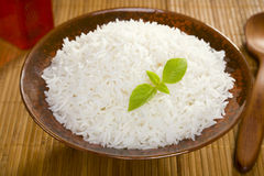 Basmati Rice. A bowl of perfectly cooked, plain Basmati rice, in an Asian style bowl, with a garnish of Thai Basil Royalty Free Stock Photo
