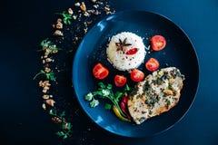 Basmati rice, anise, chili pepper, cherry tomatoes, chiken steak. Dark background, black plate, top view royalty free stock photo