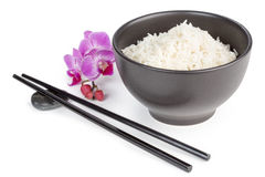 Basmati rice. Bowl of basmati rice, chopsticks and orchid flower Royalty Free Stock Photography