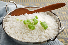 Basmati Rice and Coriander. Basmati rice in a steel karahi, garnished with coriander,with a wooden spoon Stock Photography