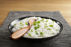 Basmati Rice with Coriander. And a wooden spoon in a black bowl, on a grey mat, on a wooden table. Traditional accompaniment to Indian curry Stock Image