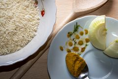 Basmati rice with curry powder and onion. Sliced in half on white plates and wooden decor Royalty Free Stock Photography