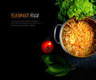 Basmati Rice Extended. Aerial view of fresh Indian Basmati coloured rice with fresh salad and tomatoes against a dark background. Extended copy space Stock Photo