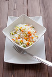 Basmati Rice with veggies. Basmati rice with carrots and courgettes in a dish on wood table Royalty Free Stock Image