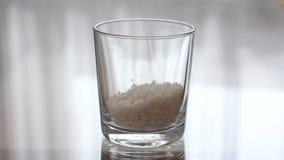 Basmati ris häller in i ett genomskinligt tomt exponeringsglas Hälla gryn i ett klart exponeringsglas arkivfilmer