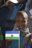 Basotho boy with Lesotho Flag. A young Basotho stands with his family and proudly  shows the National Flags H.R.H King Letsie's Birthday Parade in Lesotho Stock Photography