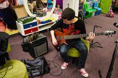 Basowy gitarzysty obsiadanie bawić się jego instrument zdjęcia royalty free